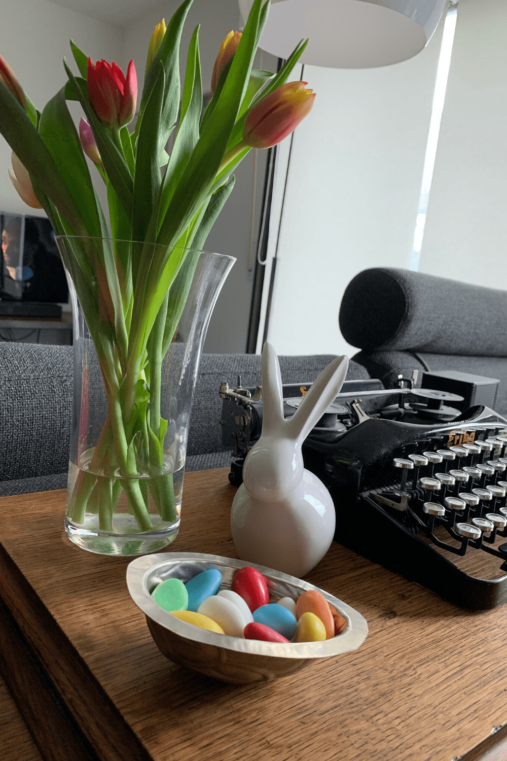 Some Scandi-inspired Easter decor on our sewing table, with a vase of tulips, vintage easter egg mould full of egg shaped jelly beans and ceramic Danish design white bunny