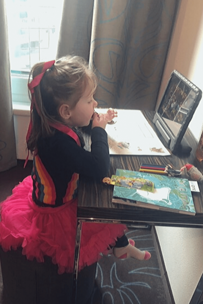 Miss M taking a break to do some colouring and watch some TV in Brussels