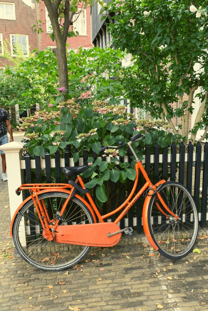 Reason #6 why Amsterdam is a great place to visit with kids of all ages: bicycles, here an orange bicycle leaning against a fence in the Begijnhof