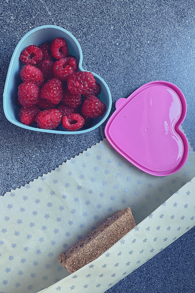 Finished environmentally-friendly wax cloth food wrap with silver stars, in use wrapping an English muffin, together with fresh raspberries in a heart-shaped container
