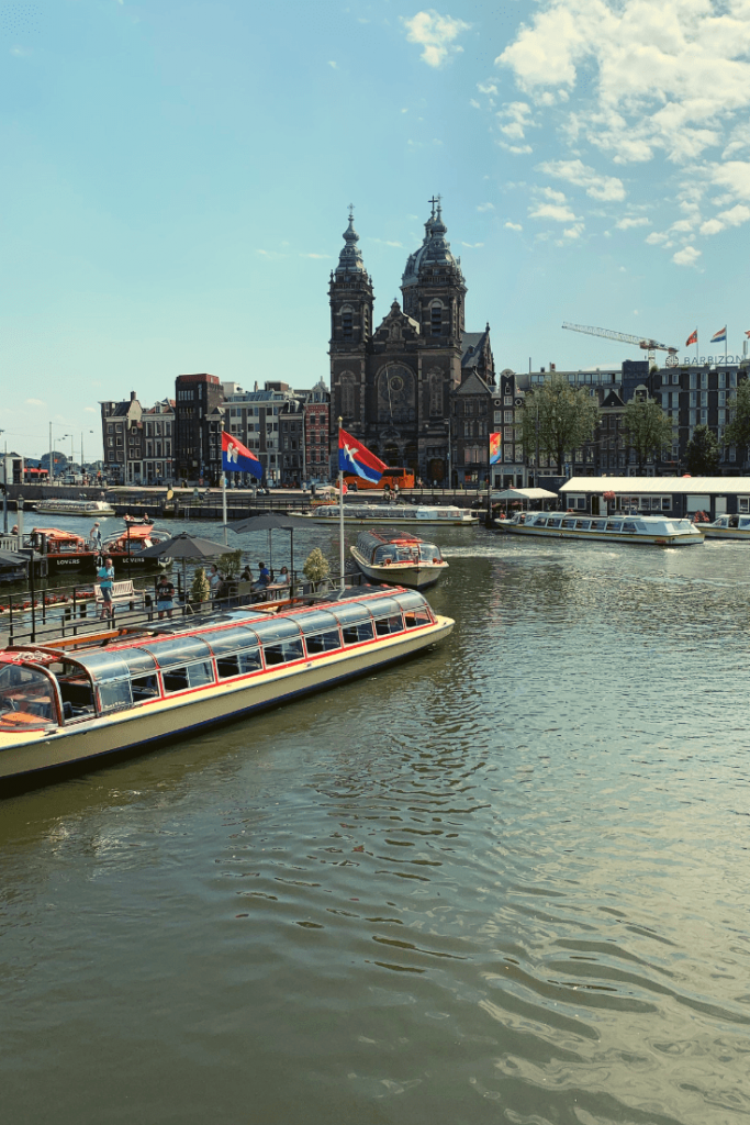 Reason #2 why Amsterdam is a great place to visit with kids of all ages: the boats and boat tours, here three tour boats in front of the Church on Damrak