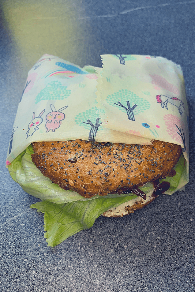 And finished! An easy, environmentally-friendly wax cloth food wrap with a unicorn forest print, used to wrap a bagel