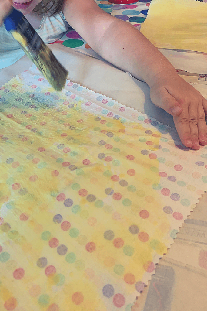 Miss M painting the spotted fabric square with our melted bees wax and coconut oil
