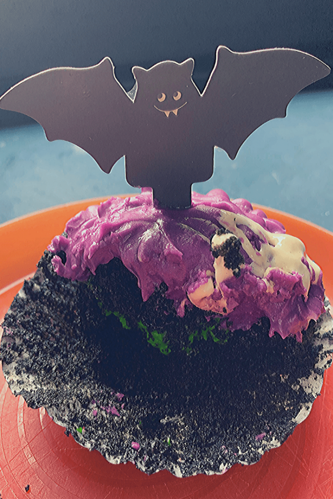 Black velvet cupcakes, with wrapper down showing the green slime (crème pâtissière), with purple cream cheese frosting, marshmallow cobwebs and bat decoration; Autumn cupcake quartet