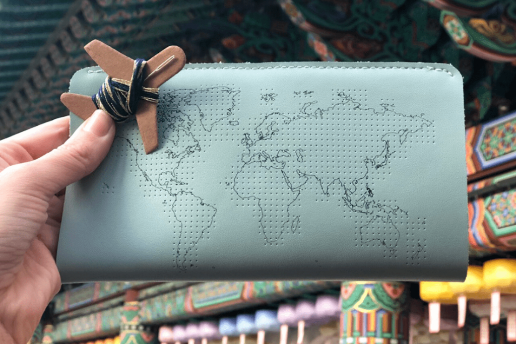 Rather than gifting a passport cover, gift a travel wallet; this fun one allows you to stitch where you have been or are going; great travel gifts for her