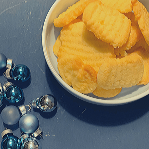 Bowl of Spritzgebäck next to some blue baubles; German Christmas biscuits; German Christmas cookies; German Spritzgebäck; Spritzgebaeck; German shortbread cookies; fresh biscuits