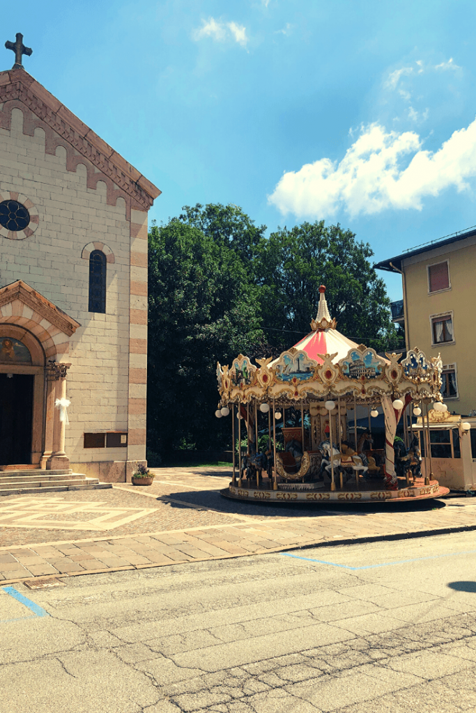 The Church of Saint Rocco and a carousel, Asiago, Italian foothills.