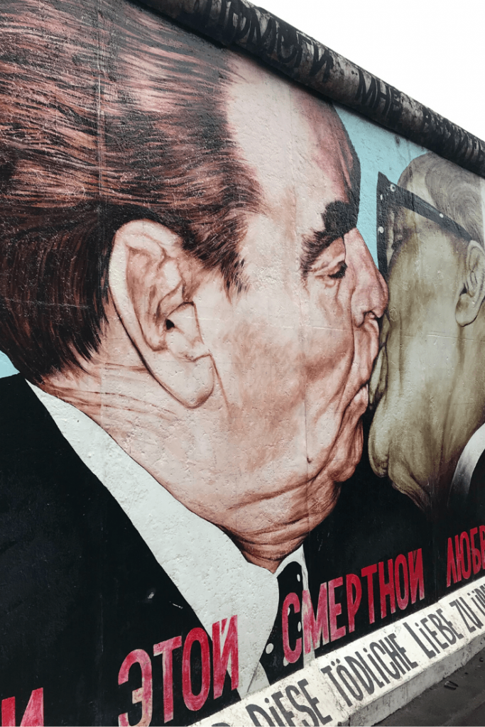 """""""The Kiss"""" or """"The Kiss of Death"""", one of the paintings on remains of the Wall at the East Side Gallery; Piece of the Berlin Wall, painted after the fall of the Berlin Wall; 30th anniversary of the Fall of the Berlin Wall; Photo by Carmel Rossen on Unsplash"""