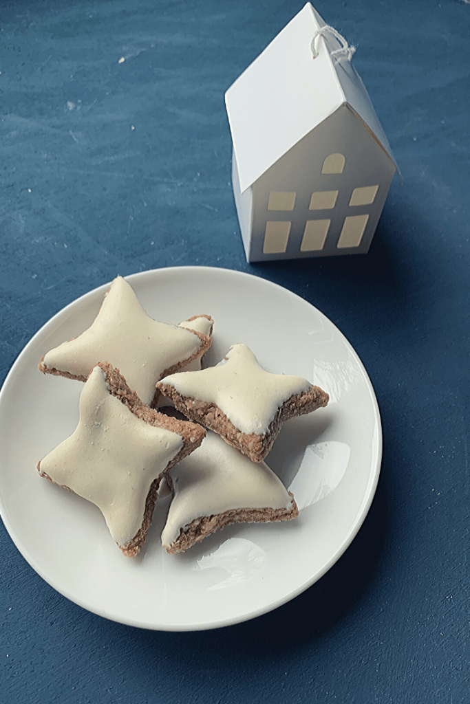 A plate of fresh German cinnamon stars - Zimtsterne - fresh cinnamon stars cooling on a rack - with paper house Christmas decoration - traditional German Christmas baking