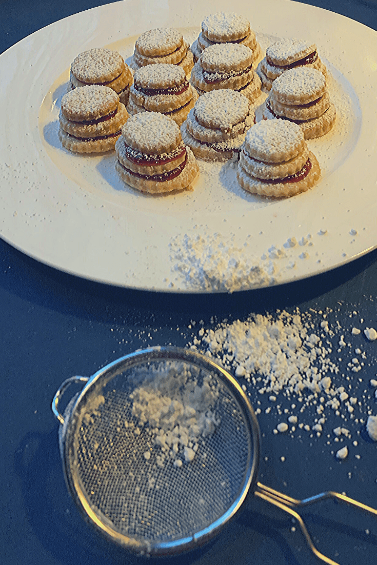 German Christmas biscuits: Terraces, or Terrassen in German; a plate of fresh terraces, dusted with icing sugar and begging to be eaten; the sieve and icing sugar form part of the image - these biscuits are easy and fun to make with kids and have a lovely subtle taste