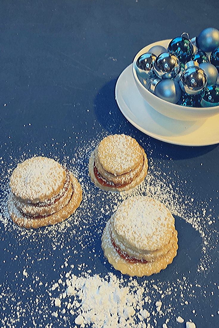 German Christmas biscuits: Terraces; three fresh terraces, just dusted with icing sugar, together with a bowl of blue ornaments - these cookies are great to make with kids and work for Christmas or any other celebration