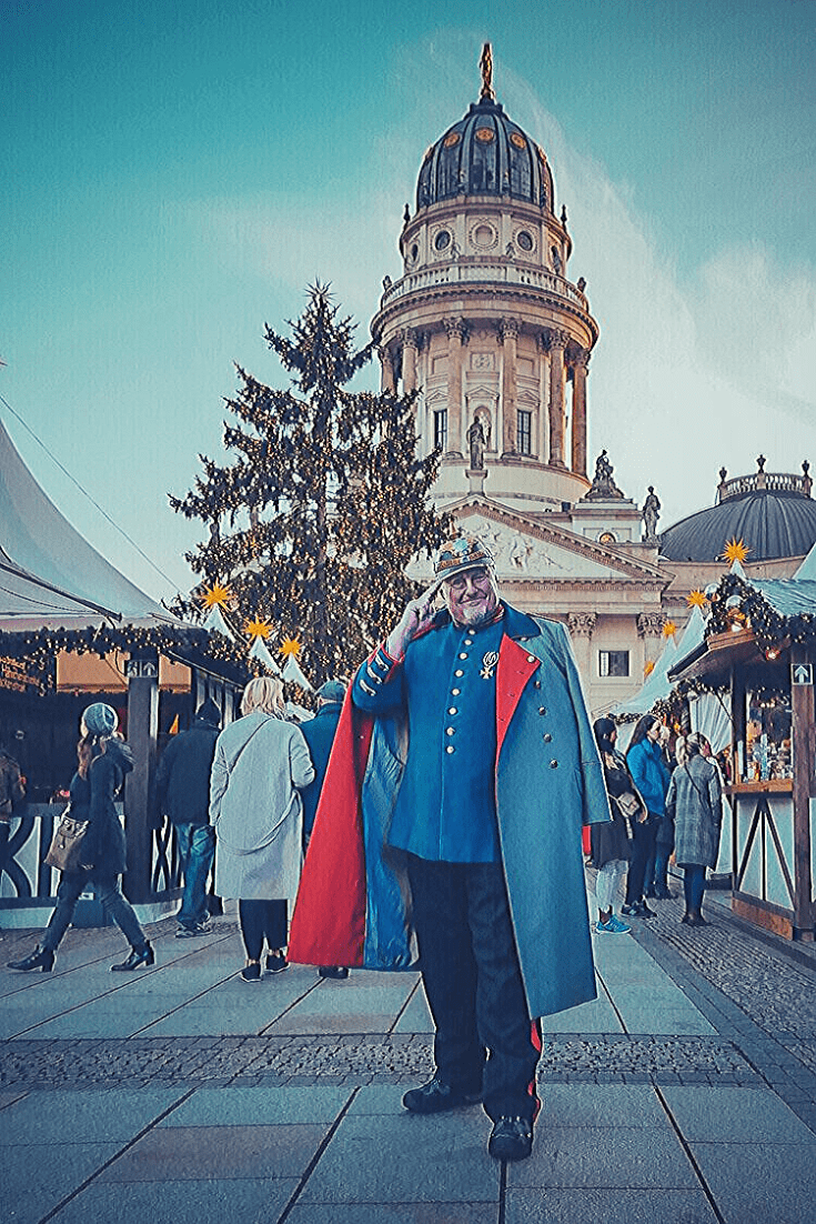 Christmas market at Gendarmenmarkt, Berlin. Man dressed up as Prussian soldier in front of German or French Dom.