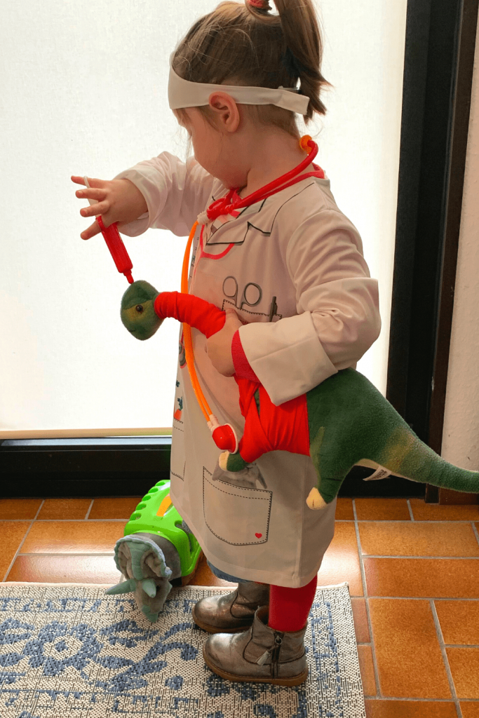 Our little dinosaur vet, in vet coat, with stethoscope, syringe and dinosaurs; little dinosaur aficionado; dino costumes for girls