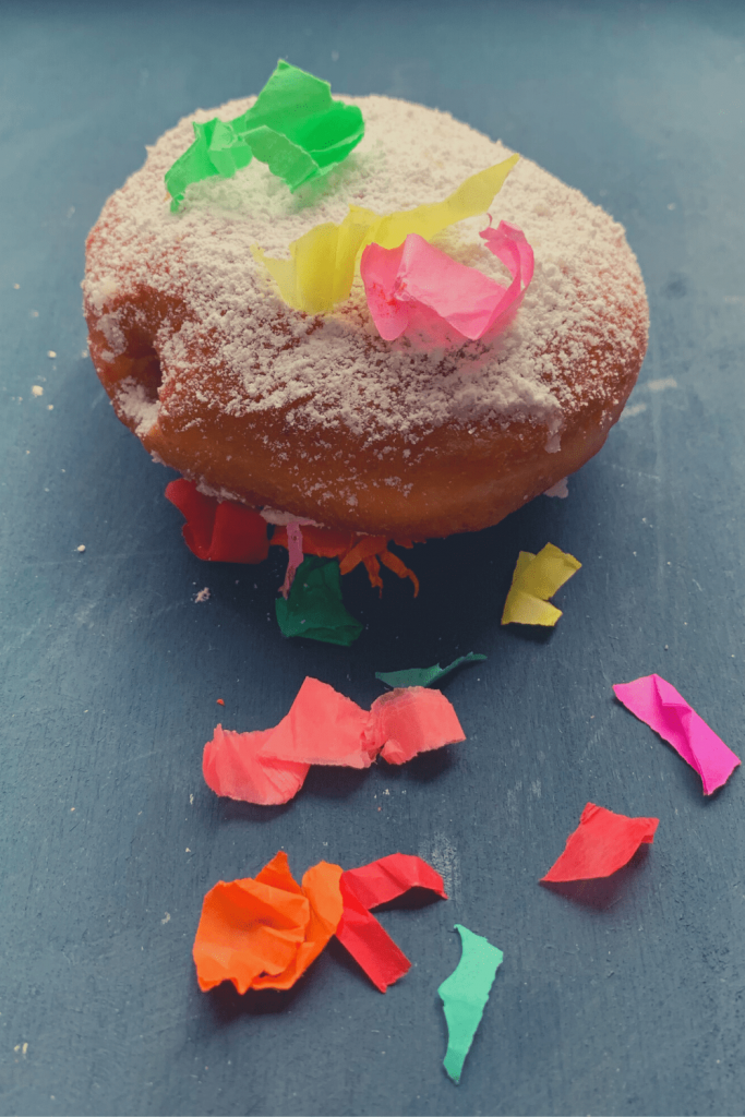 A traditional carnival treat with carnival confetti raining down on it: a simple Berliner doughnut