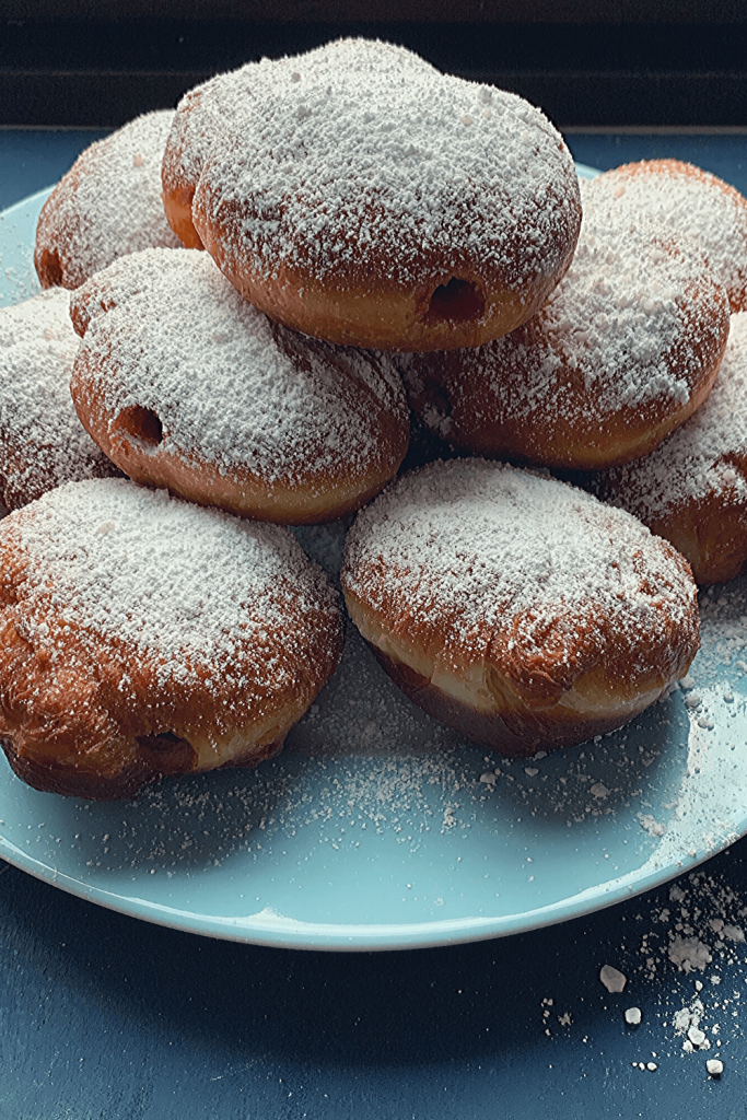 An easy recipe for traditional Berliner doughnuts; here a pile of fresh doughnuts