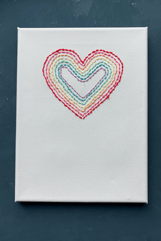 Simple Valentine's Day art; wedding anniversary artwork; heart embroidered onto white canvas in rainbow layers