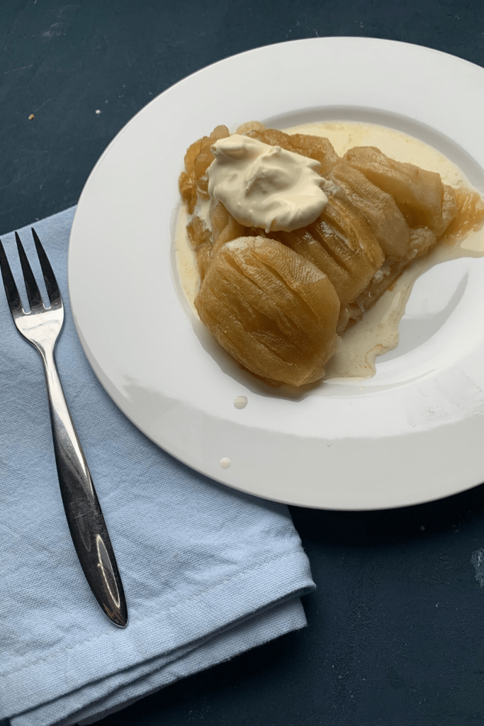 A delicious slice of maple ginger tarte Tatin, with fresh cream. Image includes a fork and a blue napkin