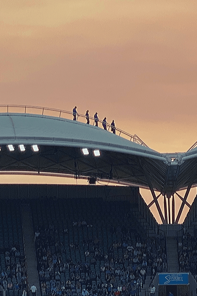 Adelaide with kids: climbers on the roof of the Adelaide Oval during a recent cricket game at sunset
