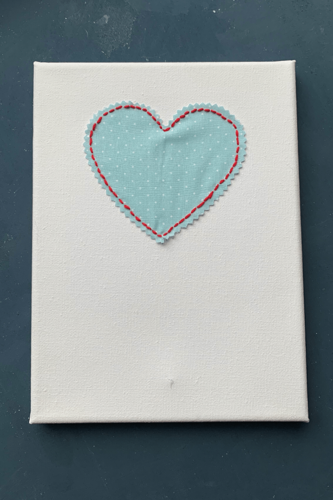 Simple Valentine's Day art; wedding anniversary artwork; blue fabric heart embroidered onto a white canvas