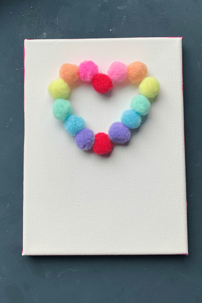 Simple Valentine's Day art; wedding anniversary artwork; love is in the air; rainbow-colored pompoms glued in a heart form onto a white canvas
