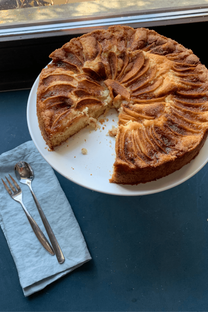 Mum's apple teacake on white cake stand in front of a window with a pale blue serviette and cake fork and spoon