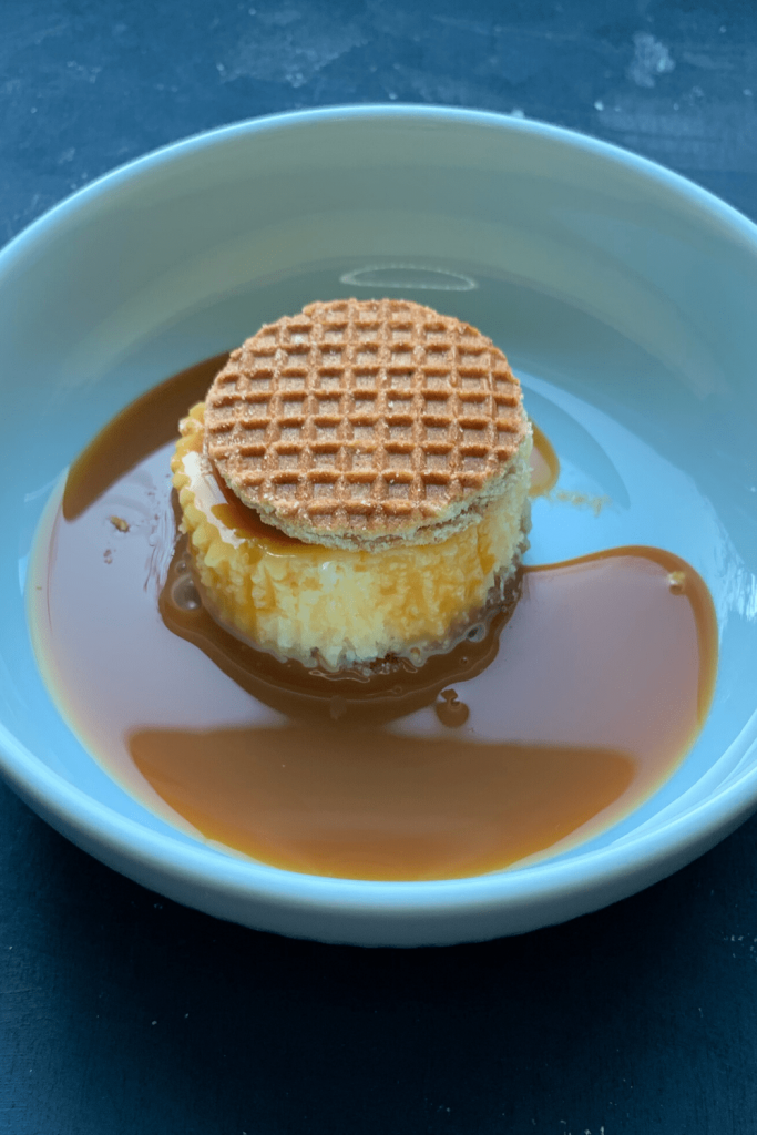 Mini stroopwafel cheesecake in a light blue bowl with a mini stroopwafel on top and lots of caramel sauce