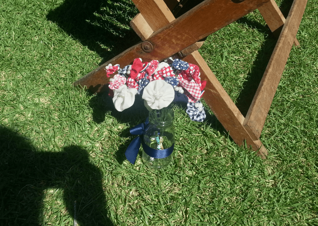 Red, cream and navy pinwheel flowers in a mini glass milk bottle on the grass next to seats for a DIY red and navy wedding.