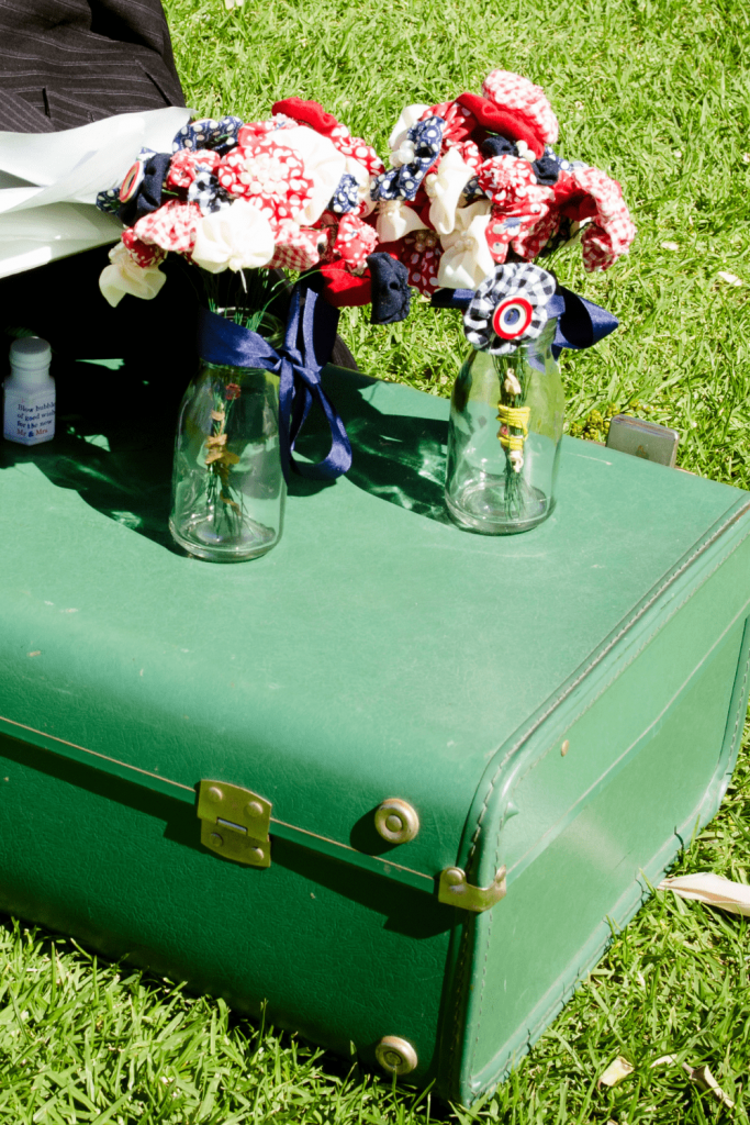 Suitcases, suitcases everywhere: 15 DIY vintage travel themed wedding ideas; pinwheel flowers on a green vintage suitcase