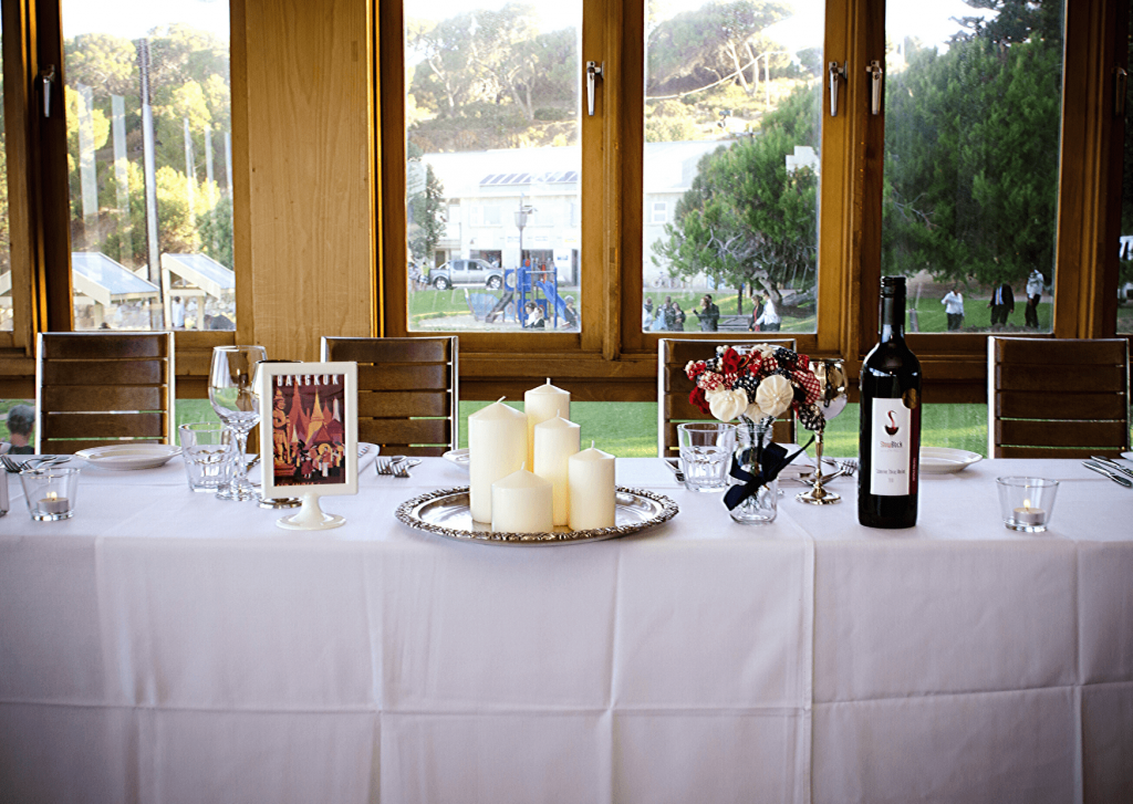 Our head table, with navy and red pinwheel flowers, vintage travel poster table name and vintage tray with candles