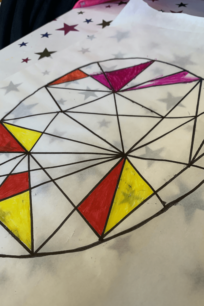 First steps for making the faux stained glass Easter art: egg outlined on grease-proof paper, lines drawn to connect the dots and the first segments coloured in