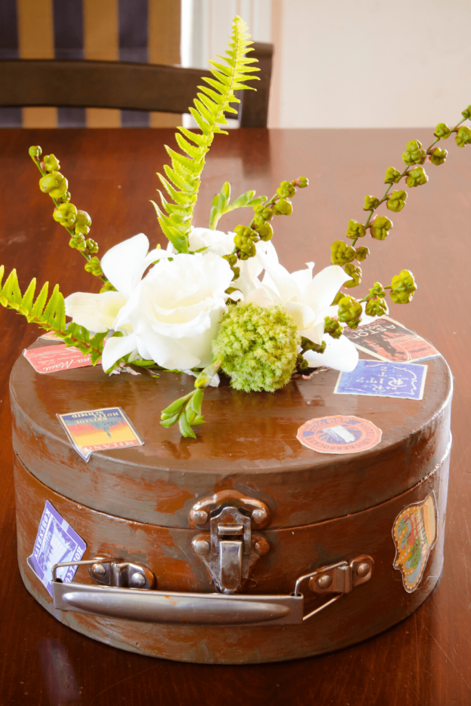 Flower girl deco patch suitcase with flowers for our vintage travel themed wedding. Photo: Kate Basso Photography