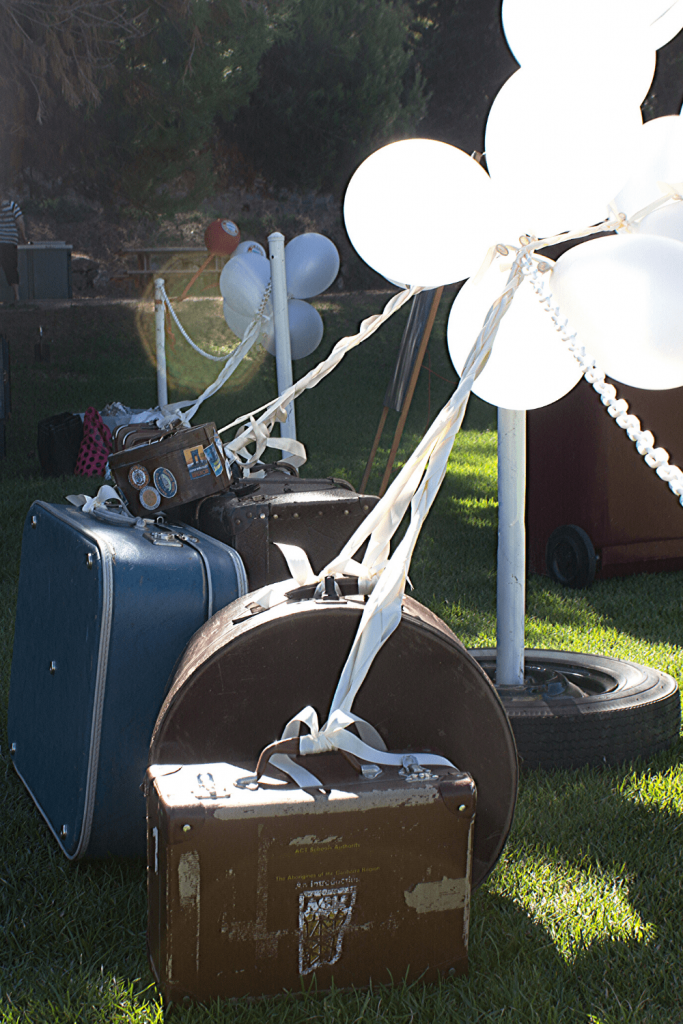 A variety of suitcases with helium balloons for our DIY vintage travel themed wedding