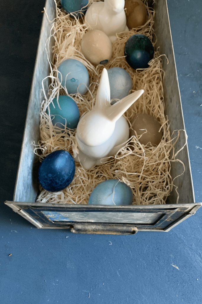 The centre of our table this Easter - at least for now: porcelain bunnies and dyed eggs in a metal drawer with straw