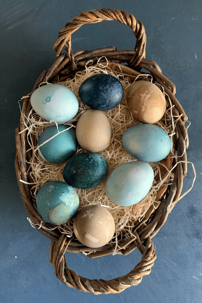 How to dye Easter eggs using natural ingredients: dyed blue and beige eggs in an Easter basket
