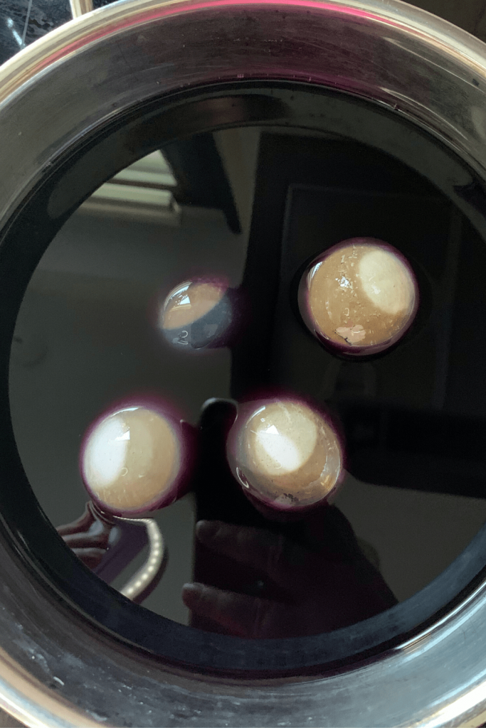 Eggs that were dyed brown with beets now being dyed purple in the blue dye