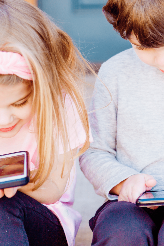Two children skyping with someone via phone
