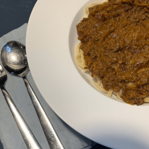Traditional spaghetti bolognese (Tagliatelle al Ragù alla Bolognese), with blue serviette and fork and spoon