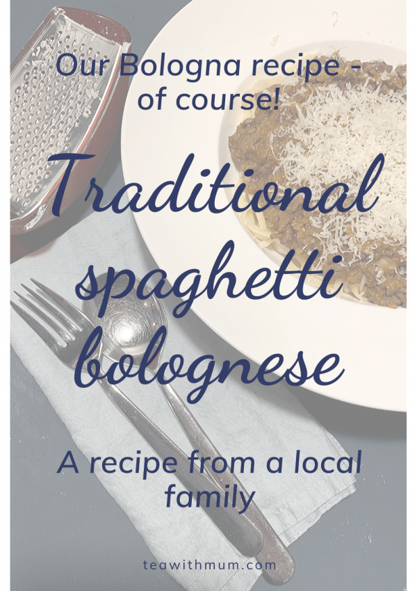 Our Bologna recipe, of course: Traditional spaghetti bolognese; a recipe from a local family; large bowl of spaghetti bolognese with parmesan cheese, a blue napkin, fork, spoon and parmesan grater
