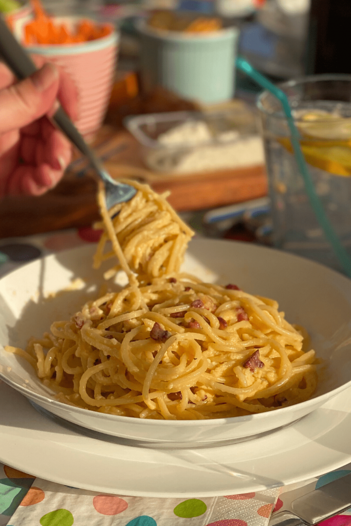 Eating traditional spaghetti carbonara with a fork