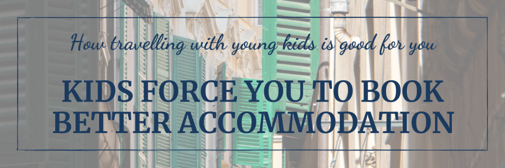 Travelling with young kids forces you to book better accommodation, or accommodation in better areas; image of street with older houses with green wooden shutters; image by Nick Fewings on Unsplash