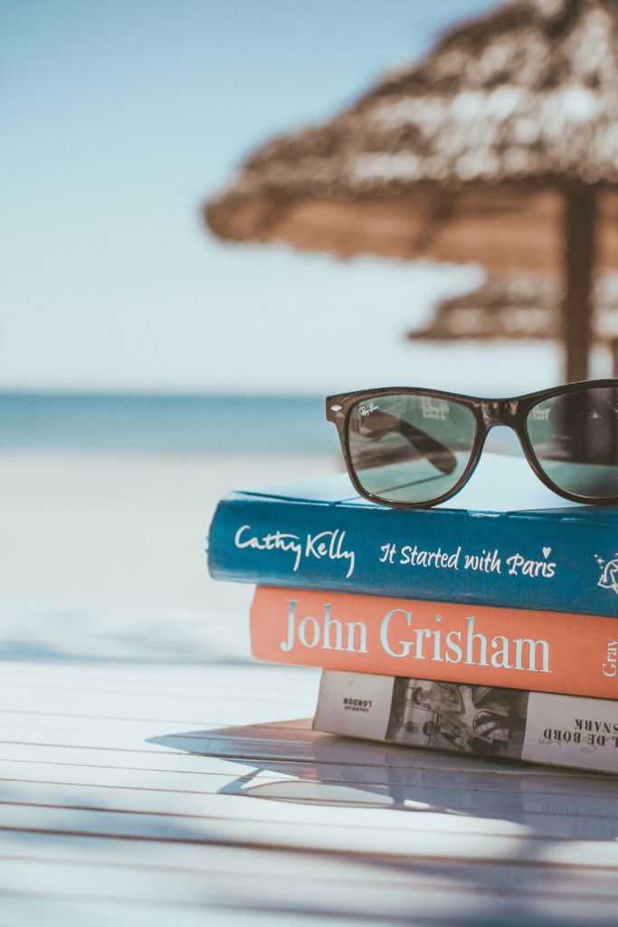 Give yourself the feeling of reading at the beach with sounds and smells and light: image of a stack of books and sunglasses overlooking the beach by Link Hoang