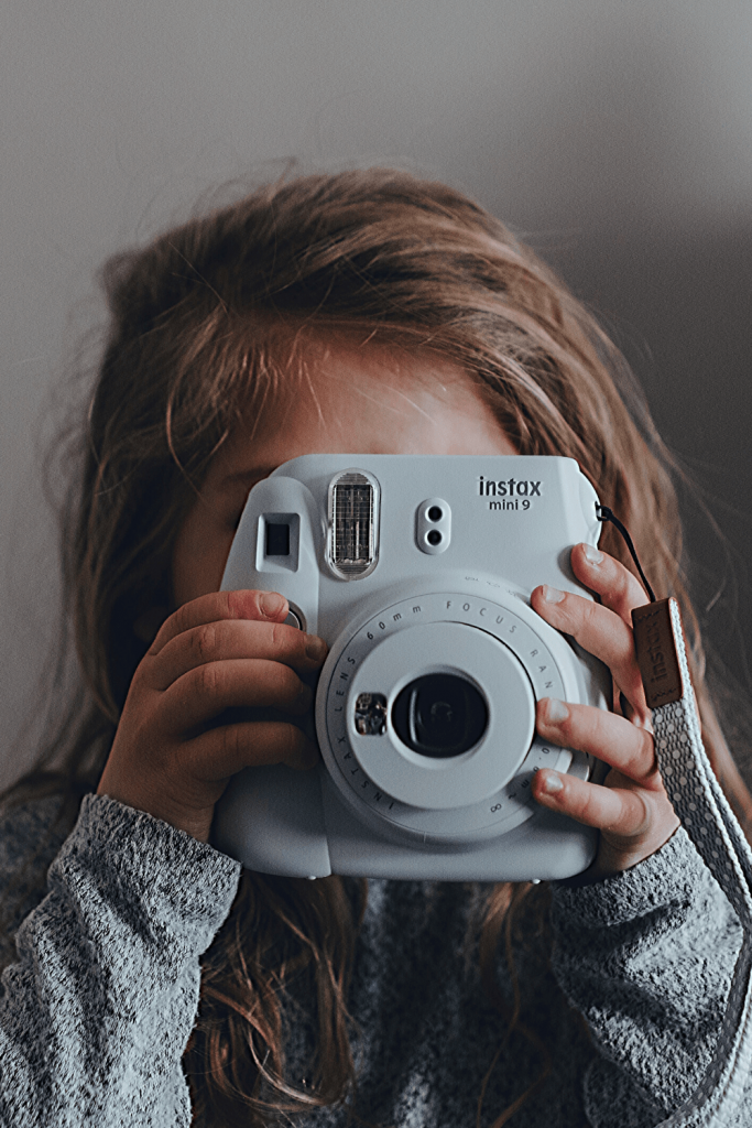 Girl with Instax camera; image y Photo by Kelly Sikkema on Unsplash
