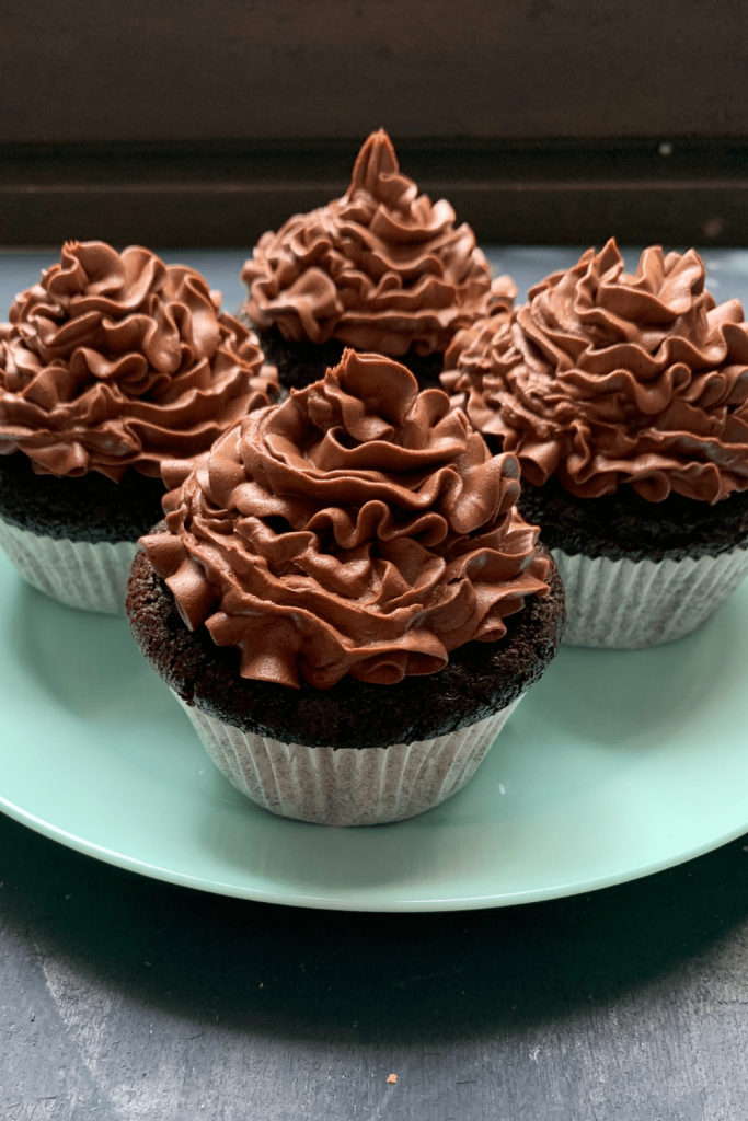 4 Depression Era chocolate cupcakes on a plate; 4 vegan chocolate cupcakes on a turquoise plate; 4 allergy-friendly chocolate cupcakes on a plate