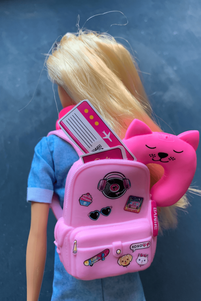 Barbie from behind with her backpack packed with toiletries, neck pillow, ticket and passport, with her headphones around her neck.