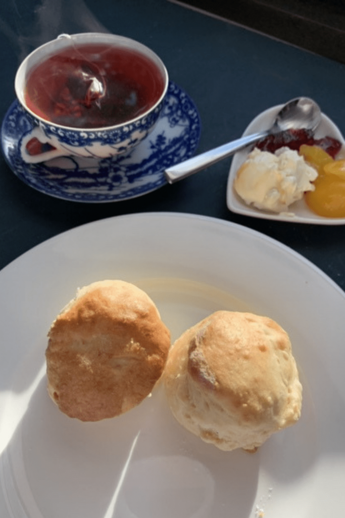 Two plain scones on a plates, with a fresh cup of steaming tea and a small heart-shaped plate with red currant jelly, lemon curd and double cream