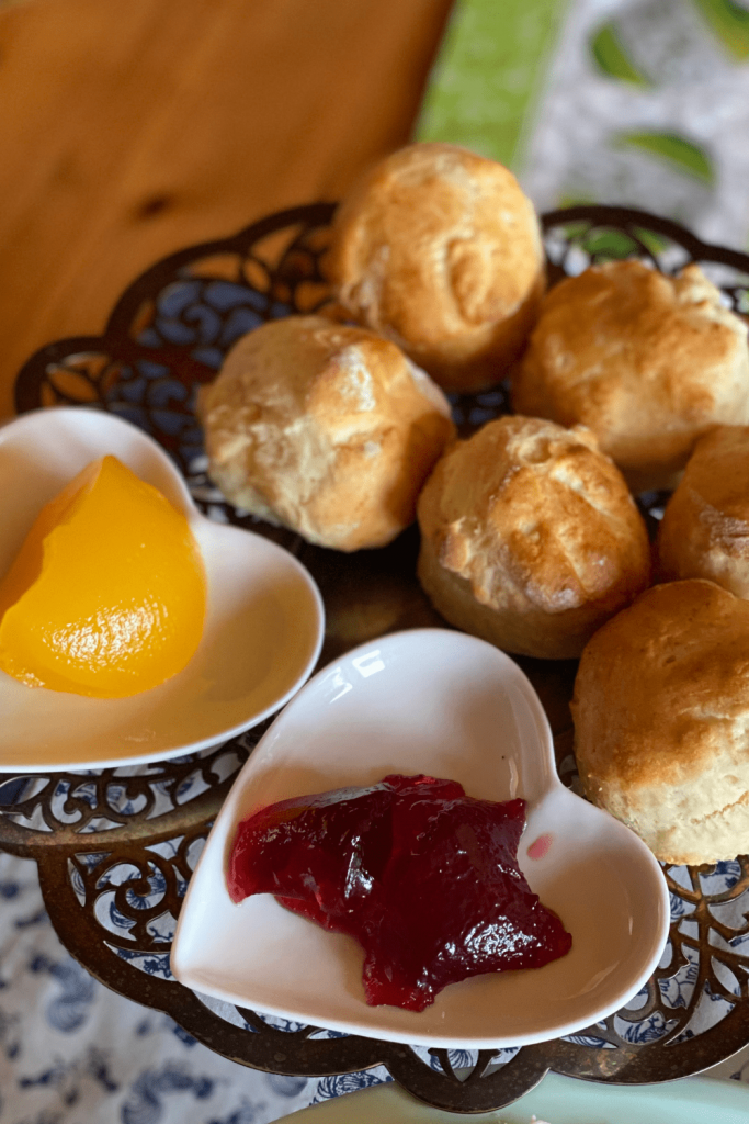Fresh easy featherlight scones on an antique cake stand, with heart-shaped bowls with red currant jelly and lemon curd