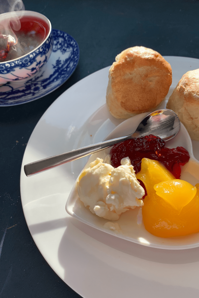 Scones with red currant jelly, lemon curd and double cream and a cup of tea