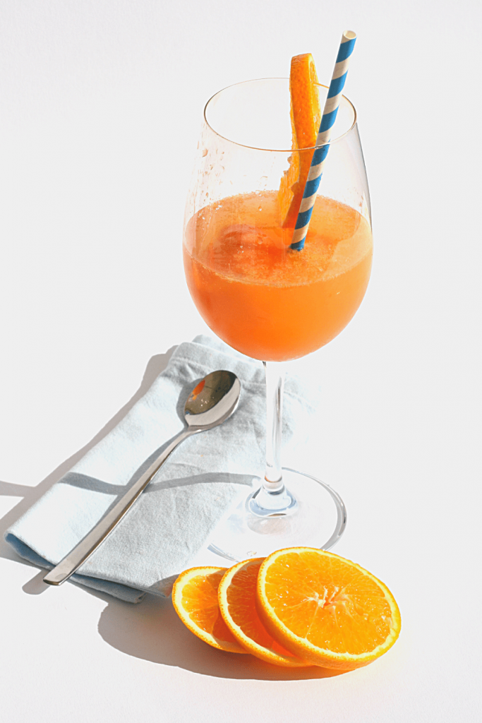 Aperol and blood orange sorbet in a glass with prosecco, a slice or orange and a blender and white striped straw