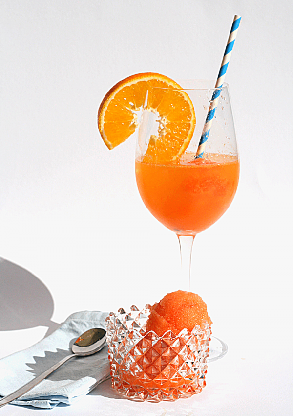 Aperol and blood orange sorbet in a bowl and in a glass with prosecco and a slice of orange