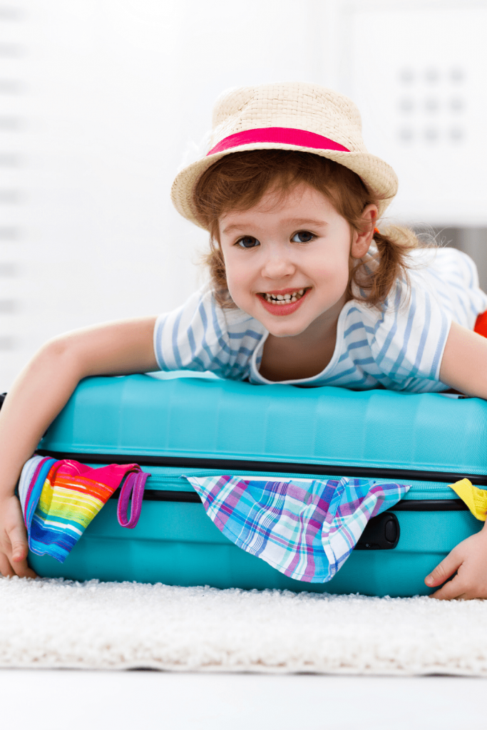 Little girl on full suitcase: How to prepare your kids for your next trip while on lockdown - practice packing